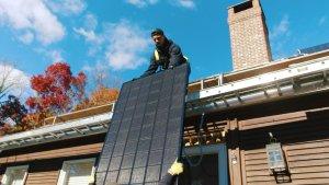 My Generation Energy solar installation team lifting solar panels onto residential rooftop