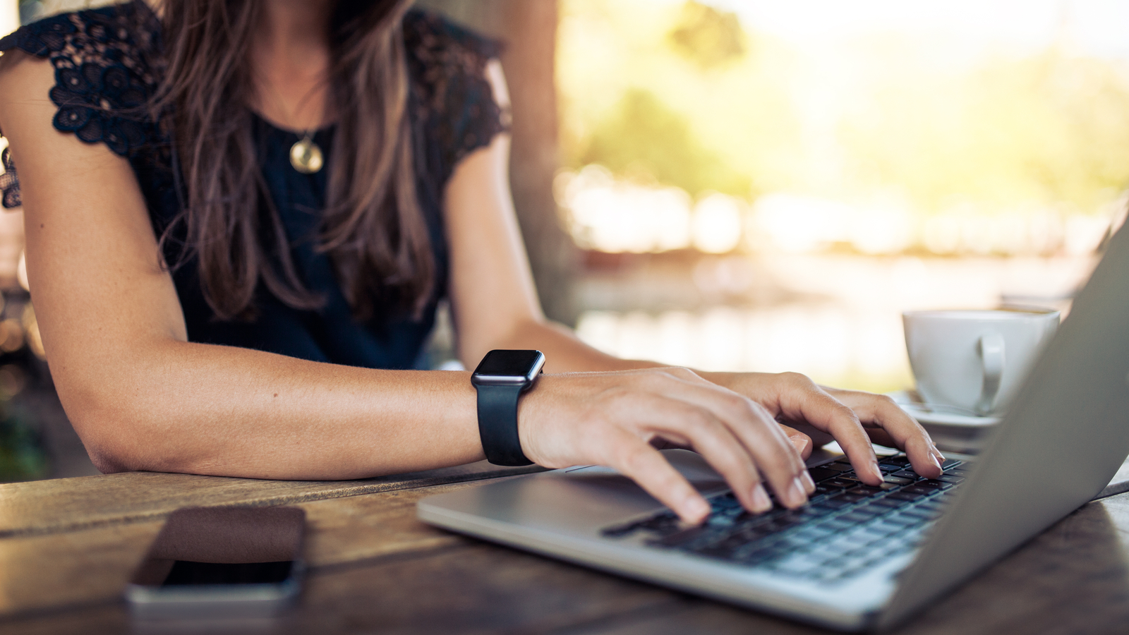 Woman with smart watch using laptop